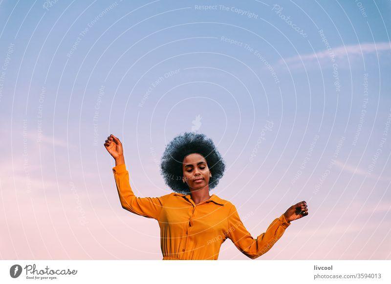 schwarze Frau, die mit dem Wind tanzt Tanzen im Freien Blauer Himmel Mädchen jung Menschen Porträt Lifestyle cool lieblich Garten gelbe Blume Außenseite Natur