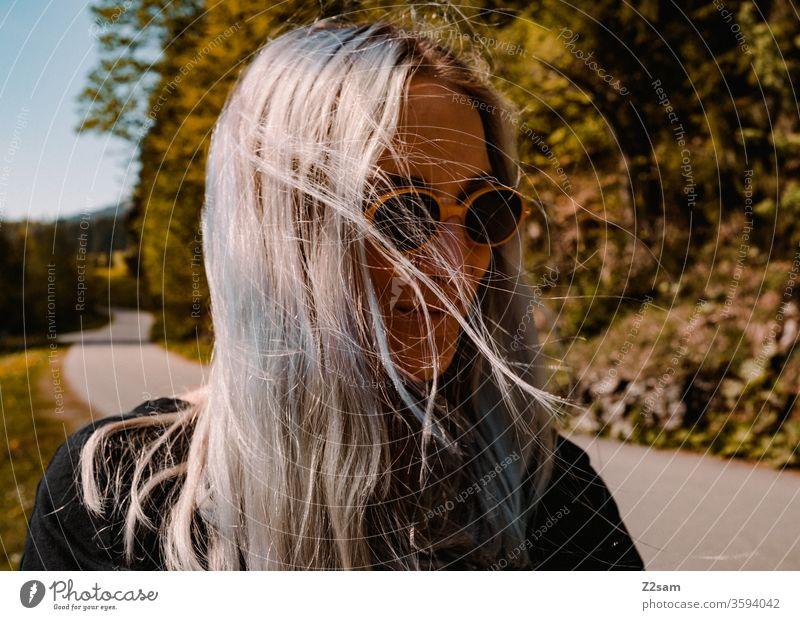 Modische Junge Frau beim Spaziergang spaziergang natur landschaft grün sommer sonnebrille retro blond lange haare schön hübsch jung jugendlich lifestyle lachen