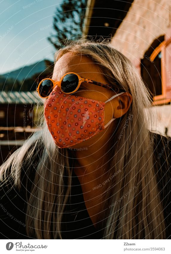 Frau mit Corona-Maske im Biergarten corona virus frau biergarten bayern schutz sonnenbrille gesundheit ansteckung soziales leben öffentlichkeit portrait blond
