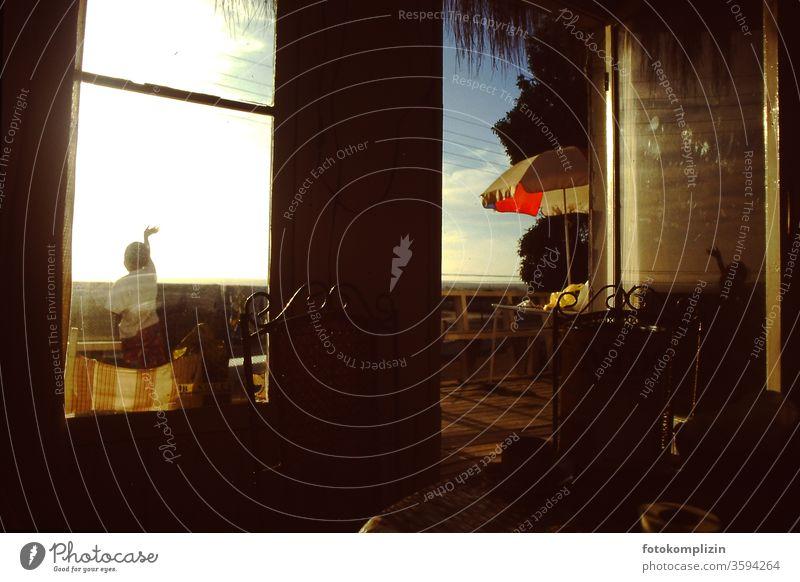 winkendes Kind auf einem Balkon grüßen Gruß Haus Art Terasse Sommer sonnenschirm Licht Sonnenuntergangsstimmung Nostalgie nostalgisch Stimmungsbild Ambiente