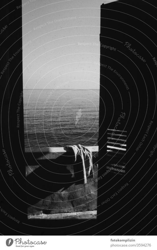 Handtuch auf Balkonbrüstung mit Blick auf das Meer Stille ozean Stilleben Wasser Strand Haus am Meer Ferien & Urlaub & Reisen Schwarzweißfoto Außenaufnahme