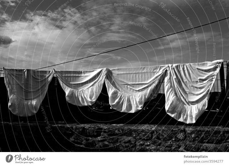 vier Spannbettlaken hängen über einen Zaun Bettlaken Wäsche Wäsche waschen Wäscheleine Haushaltsführung Häusliches Leben Waschtag Sauberkeit trocknen aufhängen