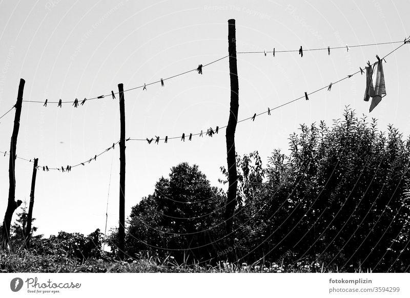 Wäscheleine mit Wäscheklammern und Pfosten als  schwarz weisse Silhouette gegen Himmel Waschtag trocknen Sauberkeit Haushalt Alltagsfotografie hängen aufhängen