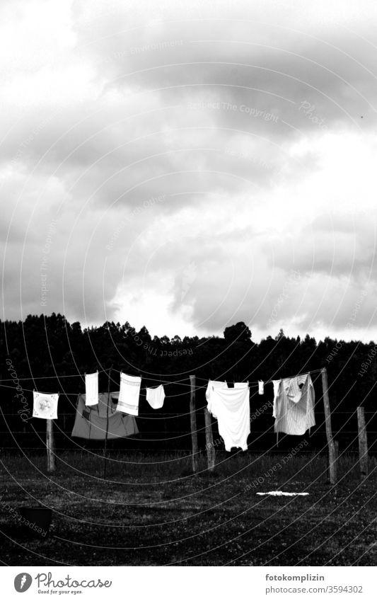 schwarz weisse Wäscheleine draußen bei bewölktem Himmel Waschtag trocknen Häusliches Leben Wäsche waschen Sauberkeit Haushalt aufhängen Bekleidung