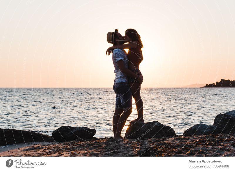 Junges Paar küsst sich bei Sonnenuntergang am Strand jung Mann Frau Kuss Küssen Liebe MEER Meer Flitterwochen Liebespaar Jungvermählte Romantik romantisch
