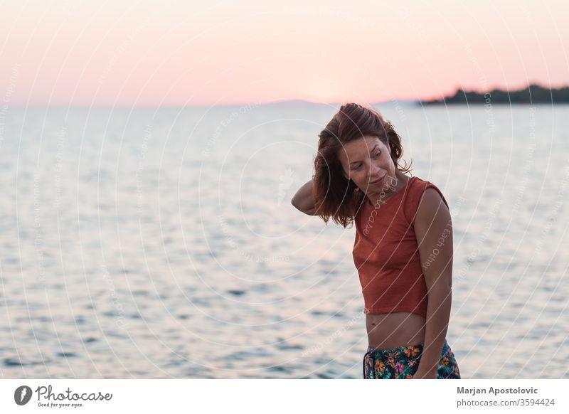 Junge Frau genießt Sonnenuntergang am Strand lässig Glück Lifestyle Sonnenaufgang MEER Meer Wasser reisen Urlaub genießend Feiertag Sommer Freiheit im Freien