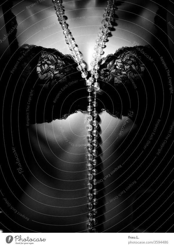 Die Glasperlenkette glitt geschmeidig vom Hals zwischen die Körbchen des Spitzen-BHs, verknotete sich dort vor Begeisterung, um dann sanft glitzernd den Nabel des flachen Bauches zu berühren.