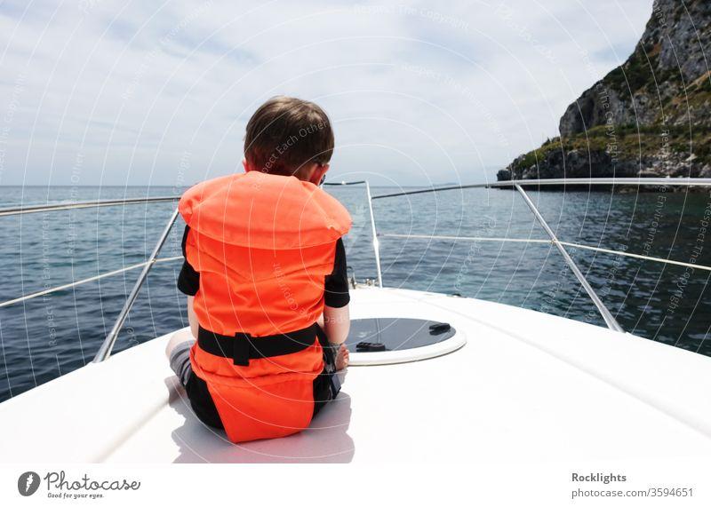 Rückansicht eines Jungen, der auf dem Deck eines Motorbootes sitzt und eine orangefarbene Schwimmweste trägt kleiner Junge Kind Sitzen Schiffsdeck Boot