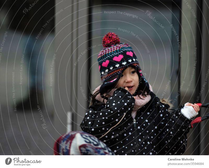 Mädchen am Staunen jung Kindheit Gesicht niedlich klein Porträt Leben erstaunt draussen staunen bunt mütze kinder träumen ausflug punkte pommel herz pink aktiv