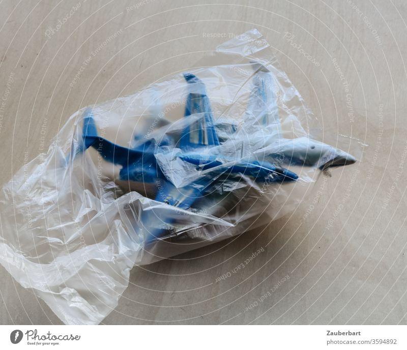 Zwei Passagierflugzeuge, Spielzeug, in einer Mülltüte als Symbol für die Krise der Luftfahrt Flugzeug transparent blau Umwelt Luftverkehr fliegen Tourismus