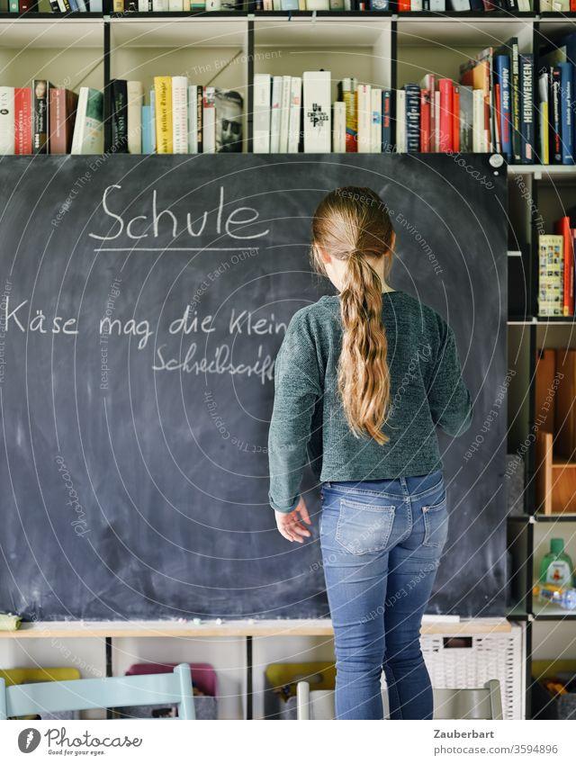 Homeschooling I - Mädchen schreibt mit Kreide auf eine Tafel einen Übungssatz für Schreibschrift, im Hintergrund Bücherregal Schule Schülerin Grundschule Regal