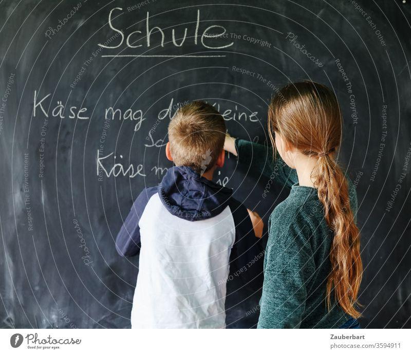 Homeschooling IV - Kinder spielen Schule, eines schreibt mit Kreide auf eine Tafel einen Übungssatz für Schreibschrift Junge Schülerin Grundschule Bücher Regal