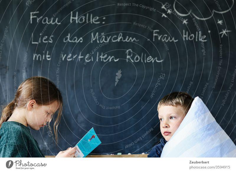 Homeschooling VI - Kinder lesen vor einer Tafel das Märchen Frau Holle mit verteilten Rollen, der Junge hält ein Kissen Schule Kindheit Schülerin Grundschule
