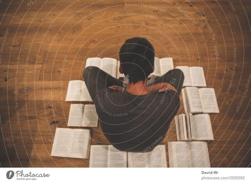 Mann sitzt auf dem Boden umringt von Büchern Buch lesen bildung gebildet lernen Parkettboden Holzboden Buchseite Bildung Studium Schule Farbfoto Weisheit