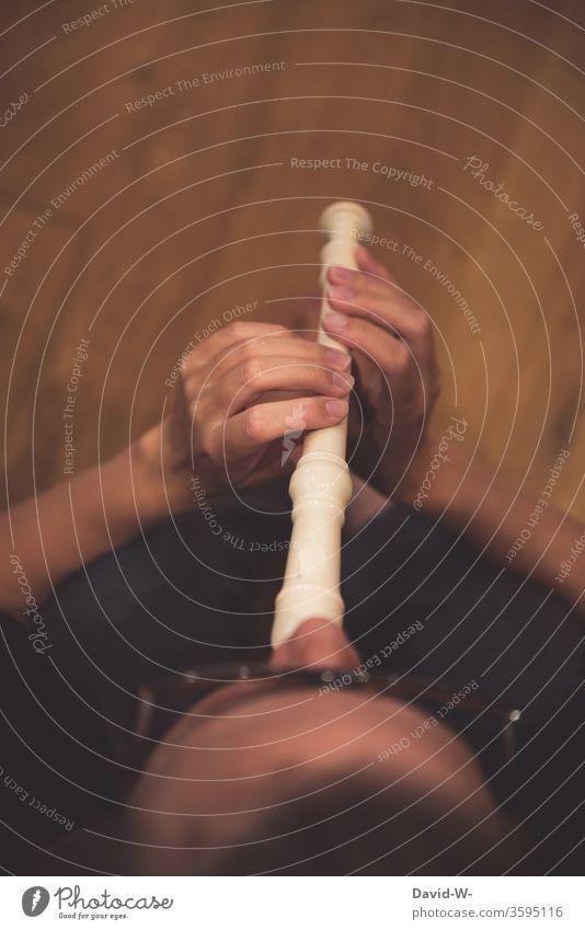 Frau spielt auf einer Flöte und macht Musik spielen Musikinstrument Vogelperspektive Musiker Musikerin Musikunterricht Brille Noten Klang Melodie töne
