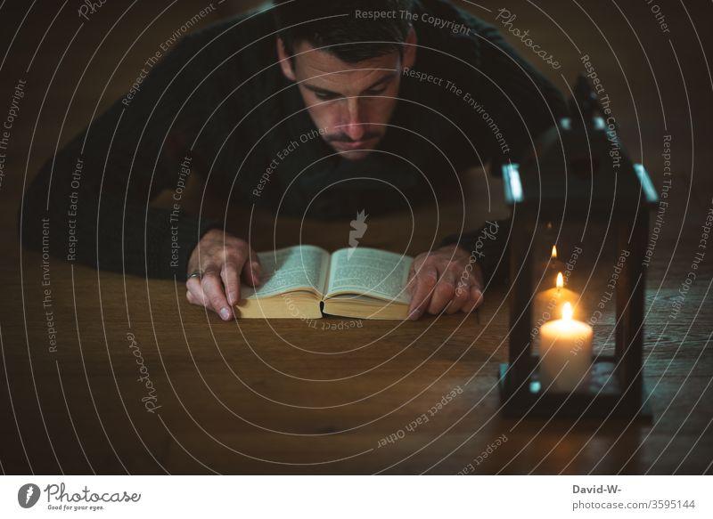 ein spannendes Buch bei Kerzenschein lesen Laterne Mann Leser Boden Literatur Bildung Studium Roman Spannung vertieft