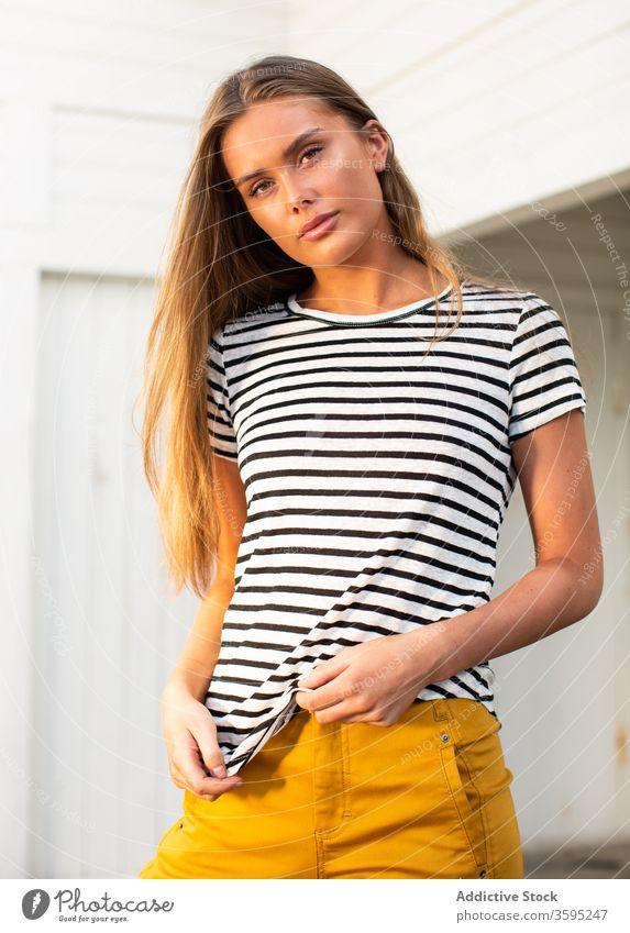 Stilvolle Frau am Kai in Gebäudenähe mit Rettungsring trendy Streifen Portwein Windstille Wand hölzern stehen jung selbstbewusst Sommer sich[Akk] entspannen
