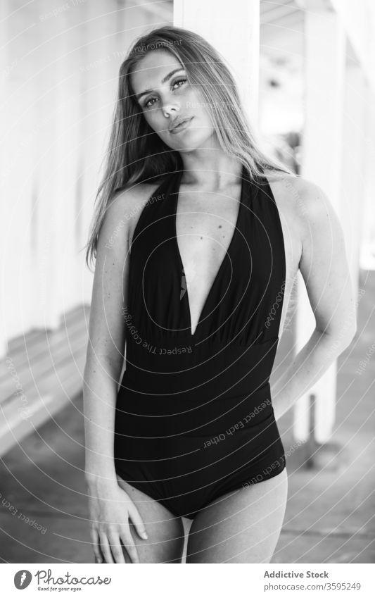 Schlanke Frau im Badeanzug am Kai Stil schlanke Badebekleidung Portwein trendy Feiertag Windstille friedlich stehen fettarm Spalte jung selbstbewusst Sommer