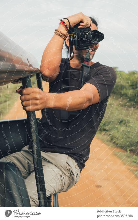 Inhalt männlicher Reisender beim Fotografieren von Landschaftsbildern Safari Mann fotografieren heiter malerisch Natur Urlaub ethnisch reisen Ausflug sitzen PKW
