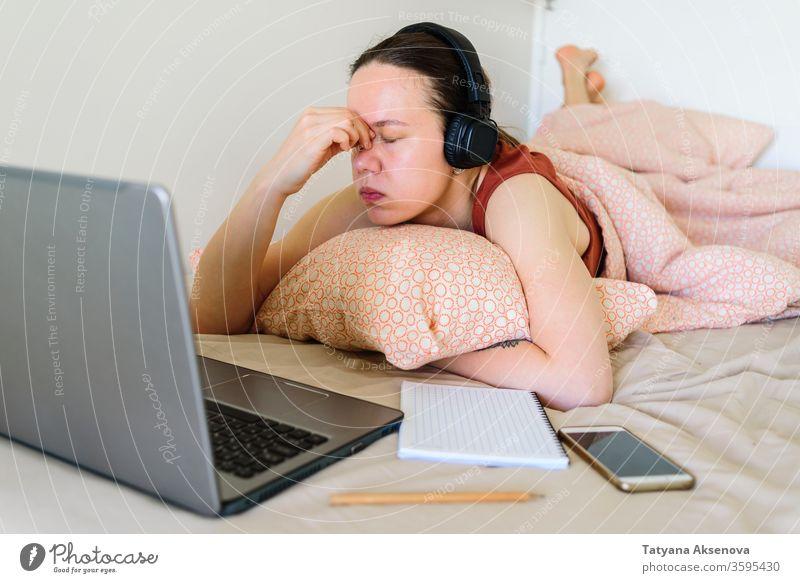 Frau, die von zu Hause aus in ihrem Bett arbeitet. Müdigkeit und Stress heimwärts Arbeit Computer Laptop Lernen müde Schlafzimmer arbeiten Business