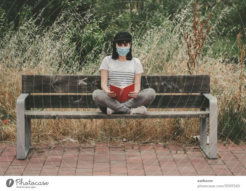Frau mit medizinischer Maske, die auf einer Bank sitzend ein Buch liest Coronavirus Junge Frau Covid-19-Virus lesen träumen sich[Akk] entspannen