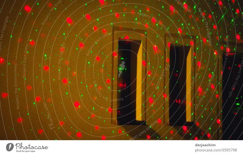 Geheimnisvolle Lichter am Haus und an den Fenstern in dunkler Nacht. Rot und Grün an der Hauswand mit Fenstern. dunkel Außenaufnahme Straße Beleuchtung Stadt