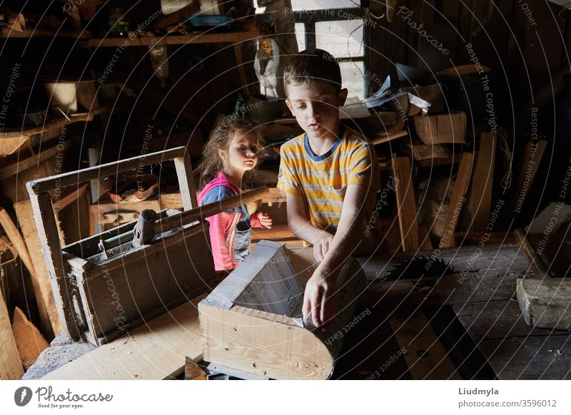 Ein Junge baut in der Schreinerei ein Vogelhäuschen aus Holz. Die neugierige kleine Schwester versucht zu sehen, was er hinter seinem Rücken macht. Heimwerker