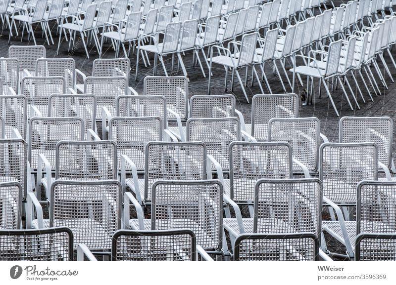 Leere Stuhlreihen einer Freilichtbühne Stühle outdoor leer weiß Diagonal Stahl Sitze Dämmerung leere Plätze keine Zuschauer Menschenleer Sitzgelegenheit