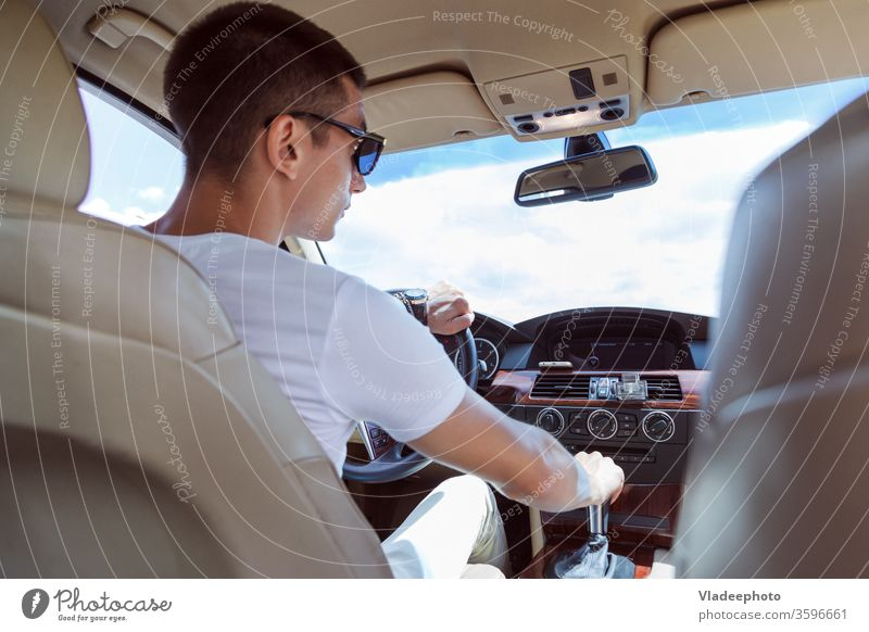 Junger stilvoller Mann mit Sonnenbrille, der ein Auto fährt. Blick von hinten, mit dem Beifahrersitz im Fond. PKW männlich Fahrzeug Automobil im Inneren Straße