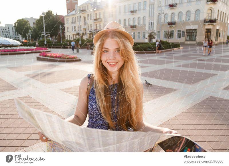 stilvolle Reisende Hipster-Frau Porträt mit Kamera und Hut haltend Karte auf der Straße Landkarte reisen Reisender Beteiligung Fotokamera stylisch erkundend