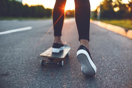 junge Skateboardfahrer mit den Beinen auf dem Skateboard Skateboarderin Mädchen Schuhe Turnschuh Frau extrem Jugend gelb Sonnenschein Sport Skateboarding USA