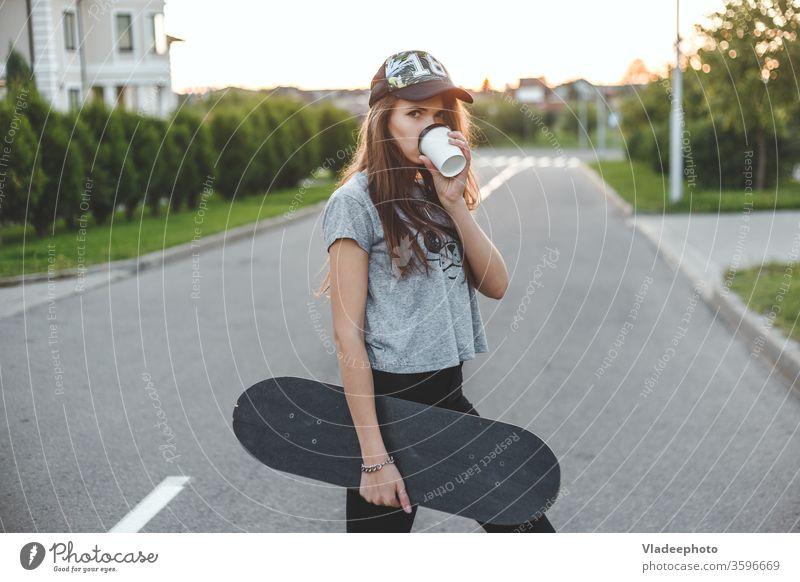 Das Mädchen mit einem aktiven Lebensstil beginnt mit Morgenkaffee und Schlittschuhlaufen. Tasse Kaffee trinken Frau Straße Stil Mode jung lässig schön im Freien