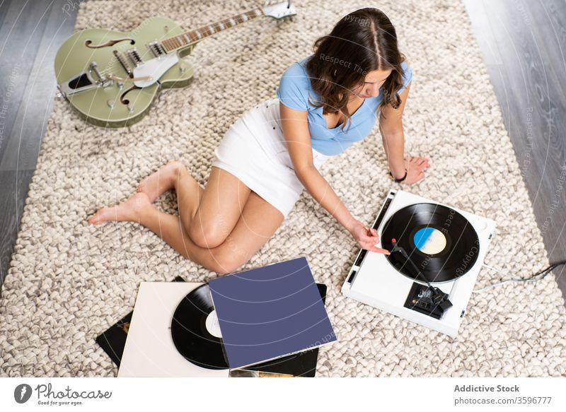 Junge Frau hört Musik auf Vinylplatte Aufzeichnen Scheibe Spieler zuhören heimwärts ruhen retro meloman jung Klang Melodie Gesang Audio Hobby Gerät unterhalten