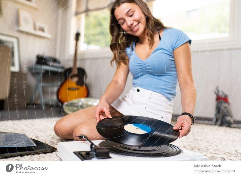 Junge Frau hört Musik auf Vinylplatte Aufzeichnen Scheibe Spieler zuhören Lächeln heimwärts ruhen retro meloman jung Klang Melodie Gesang schön Glück Audio
