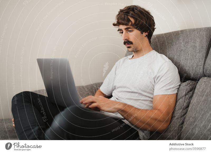 Gutaussehender männlicher Freiberufler mit Laptop im Wohnzimmer Unternehmer abgelegen Projekt Mann freiberuflich Arbeit benutzend online Konzentration heimwärts