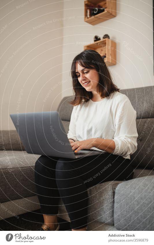 Weibliche Freiberuflerin mit Laptop zu Hause multitask Unternehmer Frau Lächeln benutzend Apparatur Glück Projekt Browsen selbstbewusst Sofa abgelegen Gerät