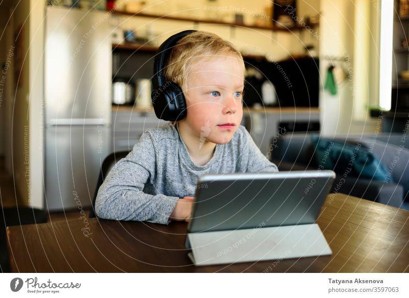 Kleiner Junge lernt zu Hause. Webinar auf einem mobilen Tablet ansehen. Bildung Homeschooling Kind online Lernen E-Learning heimwärts Entfernung zuschauend