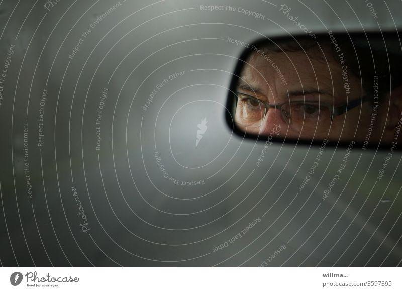Autofahren im Nebel Rückspiegel Augen Straße neblig schlechte Sicht Frau Brille konzentriert Vorsicht Unfallgefahr dunkel schlechtes Wetter Nebelstraße