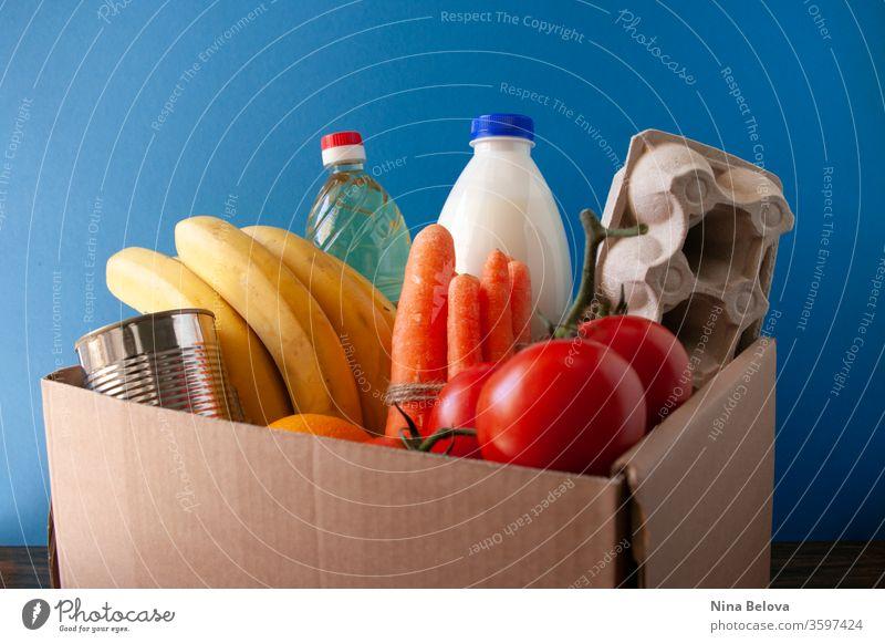 Lebensmittellieferung.box mit Lebensmittelgeschäft. Auf blauem Hintergrund. Tomaten,Bananen,Milch,Eier,Konserven,Öl. Spende. schenken Kasten Dienst Geben