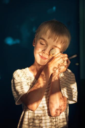 Ein kleiner Junge hält und umarmt zärtlich ein kleines Huhn in seinen Händen in der Sonne. Konzept der Tierliebe Gesicht Landwirt Hähnchen Favorit sanft