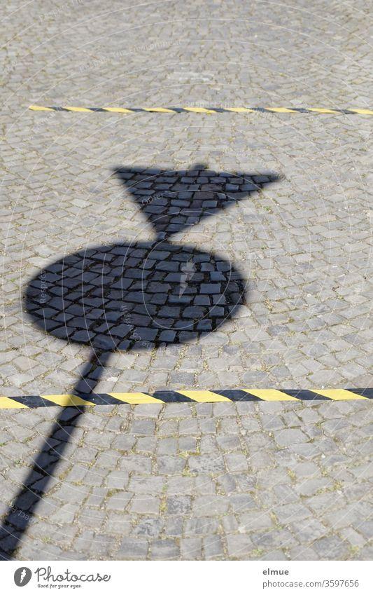 Schatten eines Verkehrsschildes auf einem gepflasterten Weg und zwei schwarz-gelbe Markierungen zur Abstandshaltung Abstand halten Infektionsschutz
