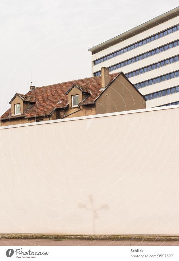 Dach eines alten Hauses zwischen Mauer mit Schatten einer Straßenlampe und neuem Bürogebäude sauber Hochhaus Gegensatz alt und neu Kontrast Architektur Wand