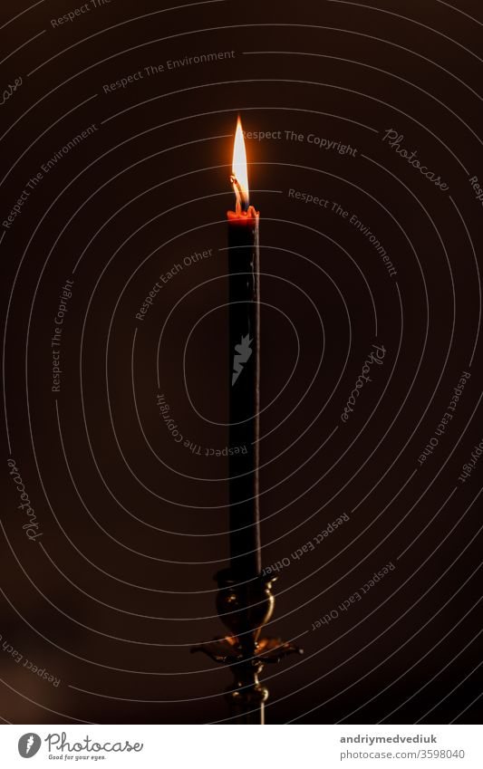eine Kerze, die nachts auf dem schwarzen Hintergrund in der Kirche brennt. Kerze isoliert auf schwarzem Hintergrund. Nahaufnahme. selektiver Fokus Kerzenschein