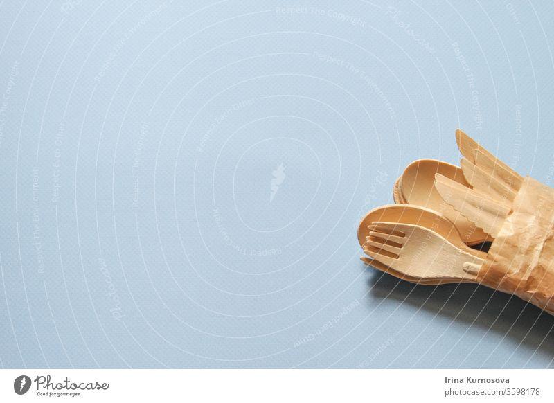 Löffel, Gabeln, Messer aus Holz auf dem blauen Hintergrund. Umweltfreundliche Einweg-Küchenutensilien aus Holz. Ökologie, Null-Abfall-Konzept. Flachlegen. Ansicht von oben