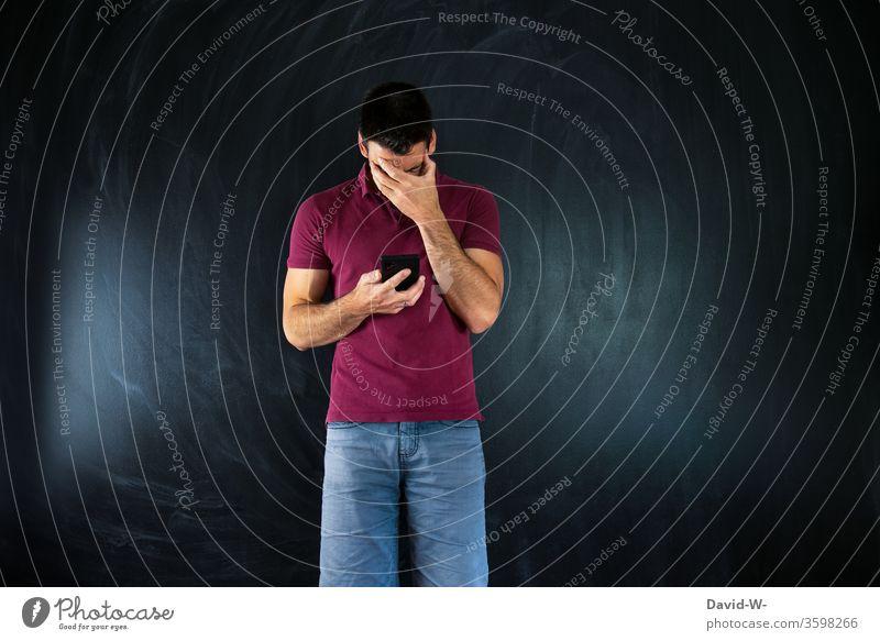 Mann mit Handy in der Hand und schlechten Nachrichten frust deprimiert angst wegschauen Hand vor dem Gesicht lesen ablesen informationen Infos news Angst Mensch