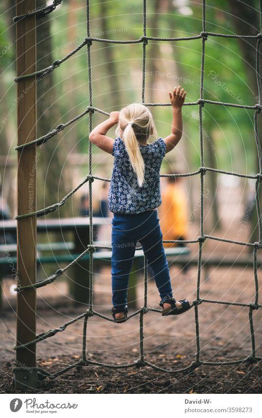 Spielplatz - Mädchen klettert ein Kletternetz hoch spielplatz freude spaß Euphorie mutig Mut festhalten festhaltend verantwortung mutig sein hoch hinaus