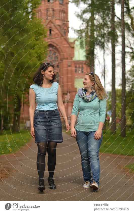 lebensnotwendig | Freundschaft – zwei junge Frauen gehen spazieren und unterhalten sich, im Hintergrund eine Kirche Freundinnen Spaziergang miteinander zusammen