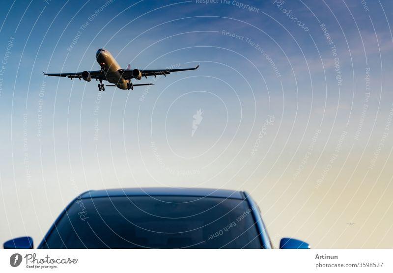 Kommerzielle Fluggesellschaft. Passagierflugzeug landet blauen Geländewagen am Flughafen mit blauem Himmel und Wolken bei Sonnenuntergang. Ankunft Flug. Urlaubszeit. Glückliche Reise. Flugzeug fliegt am hellen Himmel. Auto geparkt.