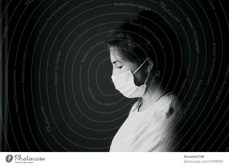 Junge Frau trägt Schutzmaske gegen Covid-19, Coronavirus sieht depressiv und isoliert aus, Schwarz-Weiß-Portrait-Virus-Konzept Hintergrund medizinisch Business