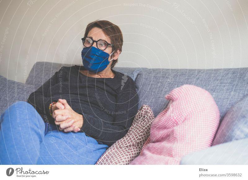 Eine Frau sitzt mit Maske zum Schutz vor einer Ansteckung mit Corona zuhause auf dem Sofa. Gesichtsmaske Porträt sitzen Virus Community-Maske Stoffmaske
